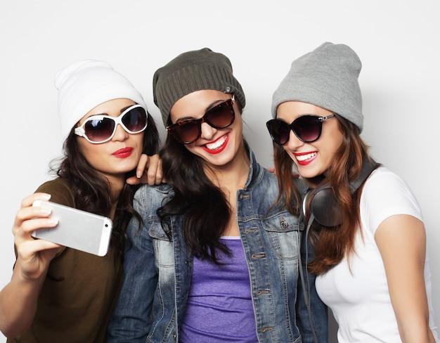 Concept d'amitié, de personnes et de technologie - trois adolescentes heureuses avec un smartphone prenant un selfie