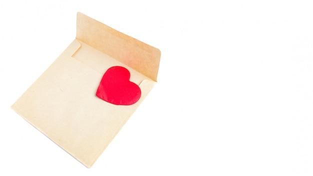 Concept d'amour: amour à distance, lettre d'amour, enveloppe d'artisanat saint valentin avec coeur rouge sur blanc