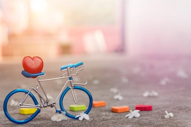 Concept d'amour; un coeur rouge et des modèles de jouets de vélo sur le sol avec le soleil