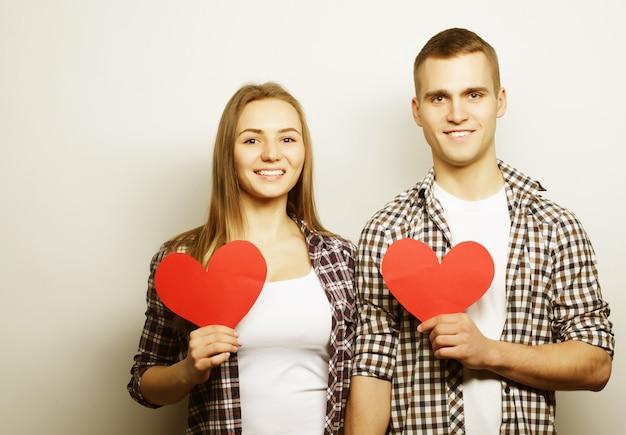 Concept d'amour, de famille et de personnes : couple heureux amoureux tenant le coeur rouge.