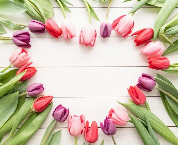 Concept d'amour. forme de coeur faite de fleurs de tulipes printanières, copiez l'espace à l'intérieur. vue de dessus à plat