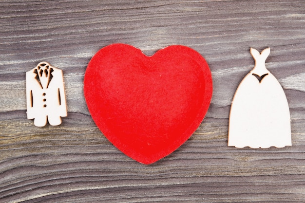 Concept d'amour et de mariage. coeur rouge et robes de mariée miniatures sur bois.