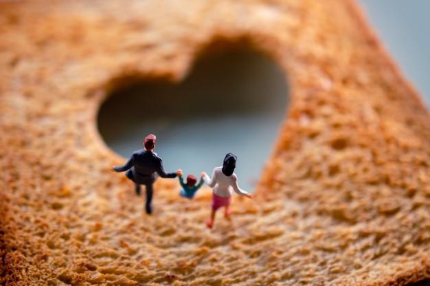 Concept de l'amour. miniature de famille heureuse marchant sur du pain grillé tranché brûlé en forme de cœur