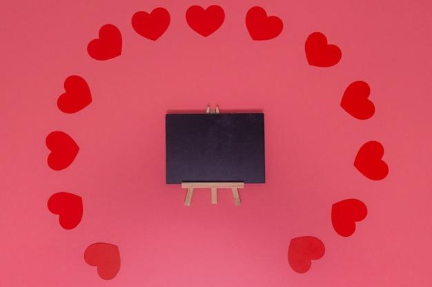 Concept d'amour. petit coeur rouge mis autour du tableau noir ceux placés sur un rose