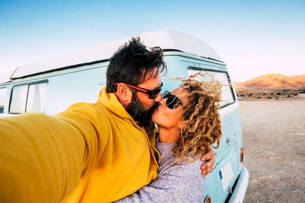 Concept d'amour et de relation avec un couple de voyageurs avec une vieille camionnette vintage s'embrassant et prenant une photo de selfie - mode de vie alternatif et.