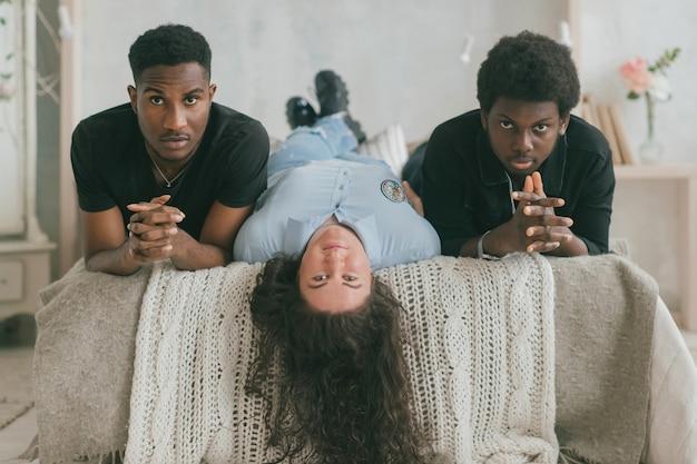 Concept d'amour et de relations multiculturelles. femme blanche allongée sur le lit avec deux hommes à la peau foncée. portrait d'intérieur d'amis interraciaux. deux hommes africains se détendre avec leur petite amie sur le lit