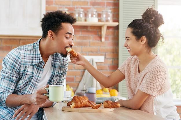 Concept d'amour et de soins. beau couple s'amuse ensemble: une femme bienveillante nourrit son mari avec un croissant,