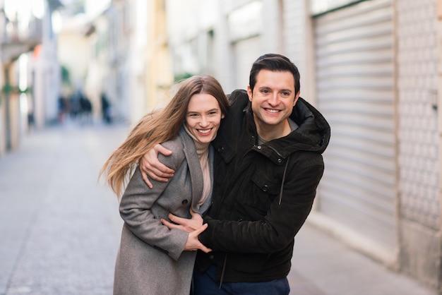 Concept d'amour, de voyage, de tourisme, de relations et de rencontres - couple heureux romantique étreignant dans la rue. vacances de la saint-valentin