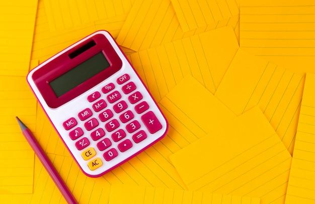 Le concept d'analyse, d'analyse, de calcul. la calculatrice repose sur des feuilles de papier orange avec un crayon