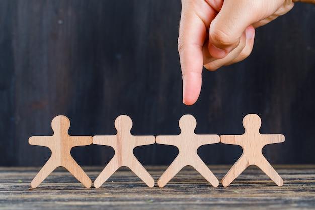Concept d'analyse marketing et client sur la vue de côté de fond en bois et grunge. doigt ciblant l'homme en bois.
