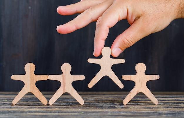 Concept d'analyse marketing et client sur la vue de côté de fond en bois et grunge. main tenant une figure en bois.