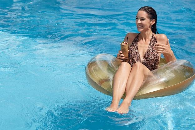 Concept d'andion d'été. jolie femme assise sur un grand anneau en caoutchouc au milieu de la piscine, tenant un cocktail à la main et regardant de côté avec une expression faciale heureuse, maillot de bain élégant habillé