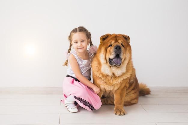Concept d'animal de compagnie, d'enfants et de famille - petite fille et sa mère étreignant le chien chow-chow sur blanc