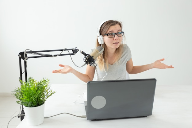 Concept d'animateur de radio, de streamer et de blogueur - femme travaillant comme animatrice de radio à la station de radio assis dans