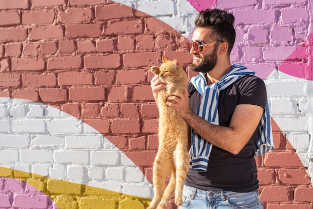 Concept d'animaux de compagnie et d'animaux - beau jeune homme avec un joli chat rouge à l'extérieur.