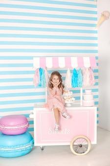 Concept d'anniversaire et de bonheur - heureuse petite fille assise sur un chariot avec de la crème glacée et des bonbons contre la barre chocolatée. grand gâteau multicolore. chambre décorée pour une fille d'anniversaire