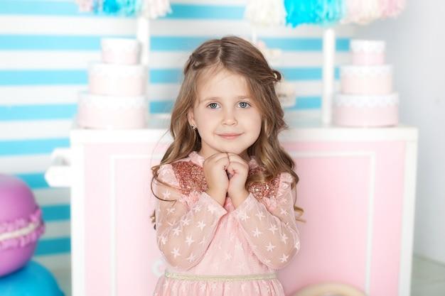 Concept d'anniversaire et de bonheur - heureuse petite fille avec des bonbons
