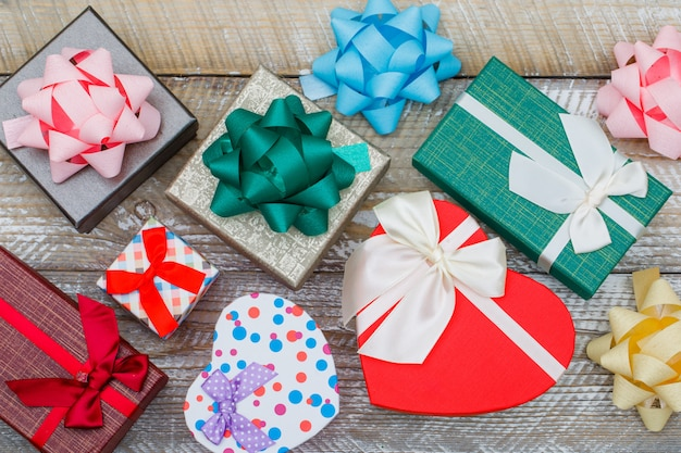 Concept d'anniversaire avec coffrets cadeaux assortis, arcs sur fond plat en bois.