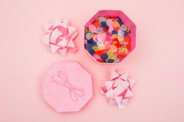 Concept d'anniversaire avec des confettis dans une boîte cadeau, arcs sur fond plat rose poser.