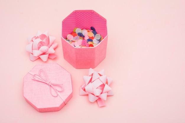 Concept d'anniversaire avec des confettis dans une boîte cadeau, arcs sur fond rose vue en plongée.