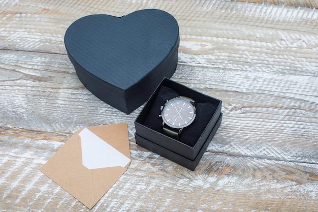 Concept d'anniversaire avec enveloppe, coffrets cadeaux avec montre sur fond en bois vue en plongée.