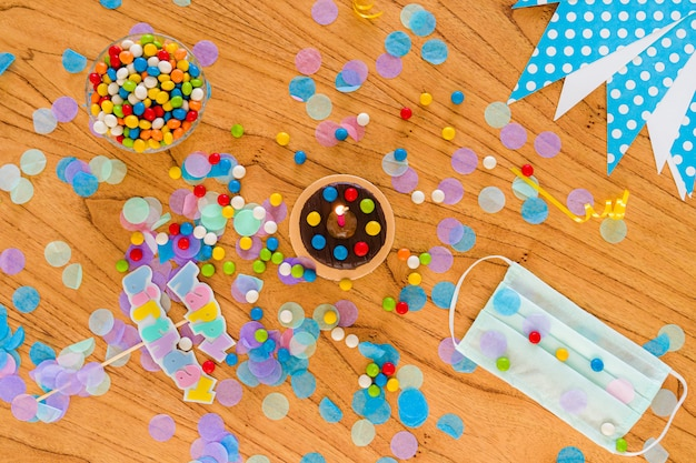 Concept d'anniversaire en quarantaine. covid19. masque chirurgical, chocolats, confettis et articles de fête éparpillés sur la table. vue de dessus