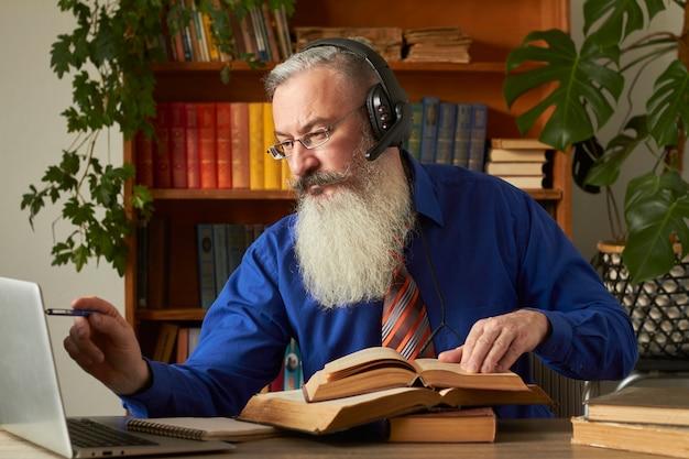 Concept d'apprentissage à distance. professeur professeur tuteur enseigne la discipline en ligne. un homme barbu mature répond à la question de l'enseignant via un ordinateur portable.