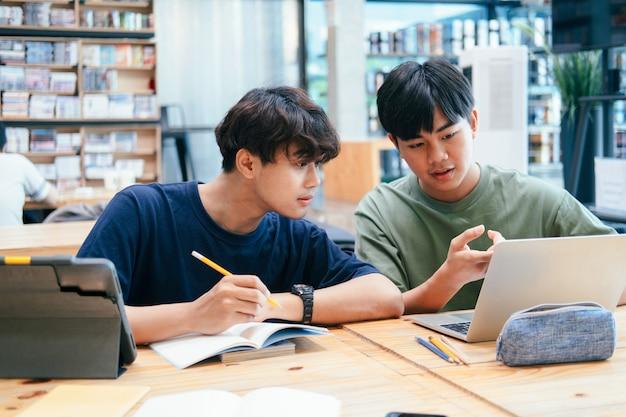 Concept d'apprentissage, d'éducation et d'école. jeune femme et homme étudiant pour un test ou un examen. livres de tuteur avec des amis. le campus des jeunes étudiants aide les amis à se rattraper et à apprendre.