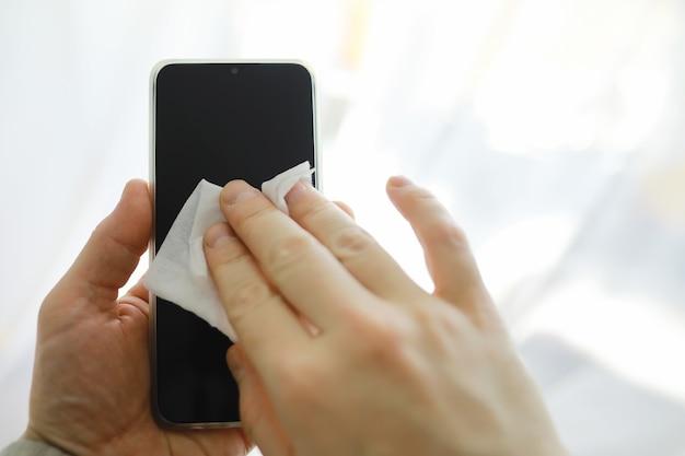 Concept d'apprentissage. essuyez la saleté des surfaces. traitement désinfectant de l'écran du téléphone. traitement sanitaire à domicile en quarantaine.