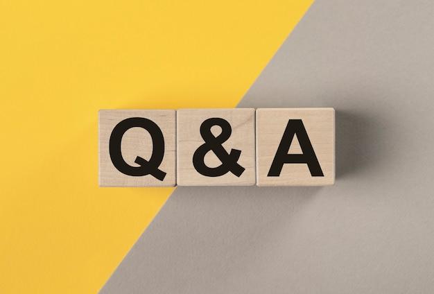 Concept d'aq ou de q. acronyme qna sur des cubes en bois sur une surface grise et jaune avec espace de copie.