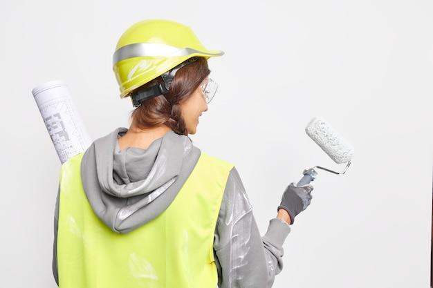 Concept d'architecture et de construction. femme dans un casque de protection uniforme de sécurité peint quelque chose avec un rouleau détient des travaux de plan sur le projet. le réparateur occupé prend du recul