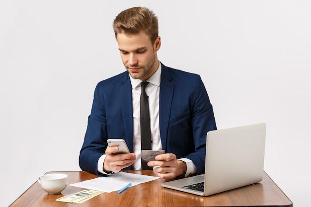 Concept d'argent, d'affaires et de finances. beau jeune entrepreneur masculin assis au bureau à l'aide d'un smartphone pour payer les factures, faire un achat en ligne, détenant une carte de crédit, fond blanc