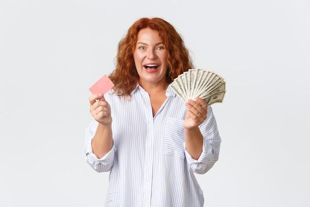 Concept d'argent, de finances et de personnes. femme rousse d'âge moyen gaie et excitée en chemisier décontracté, tenant de l'argent et une carte de crédit avec un sourire optimiste, debout sur fond blanc.