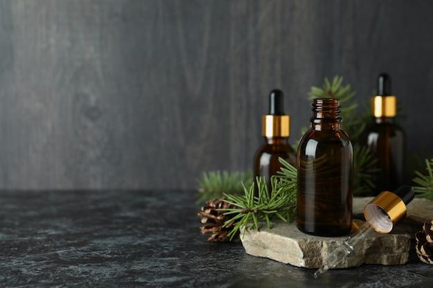 Concept d'aromathérapie à l'huile de pin sur table noire fumée