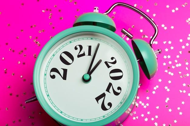 Le concept d'arrière-plan du nouvel an se transforme en réveil sur fond rose avec des paillettes festives...