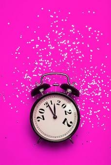 Le concept d'arrière-plan du réveillon du nouvel an se transforme en réveil sur fond rose avec un fond festif ...