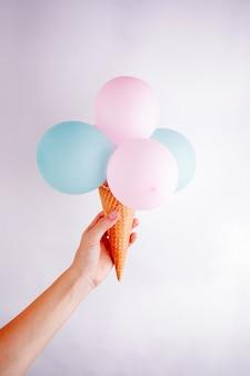Concept d'art contemporain. air baloons glaces à la main de la femme. projet minimal drôle de restauration rapide