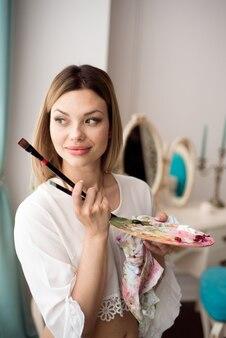 Concept d'art, de créativité, de passe-temps, d'emploi et d'occupation créative. artiste féminine posant devant la fenêtre et peignant avec de la peinture à l'huile ou acrylique