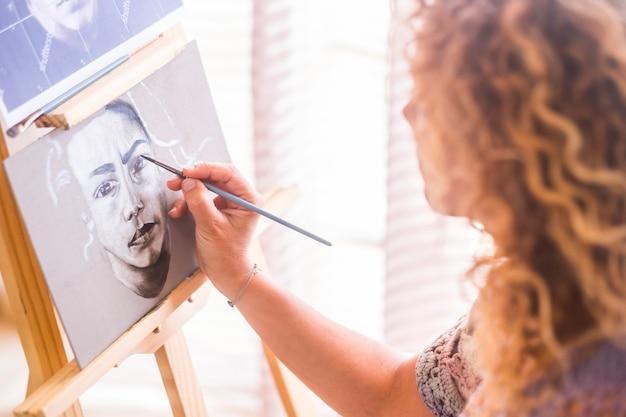 Concept d'art, de créativité et de personnes - gros plan caucasien de femme peignant à la main et dessinant un portrait à la maison en noir et blanc - activité de loisirs artistique - pinceau sur toile pour créer