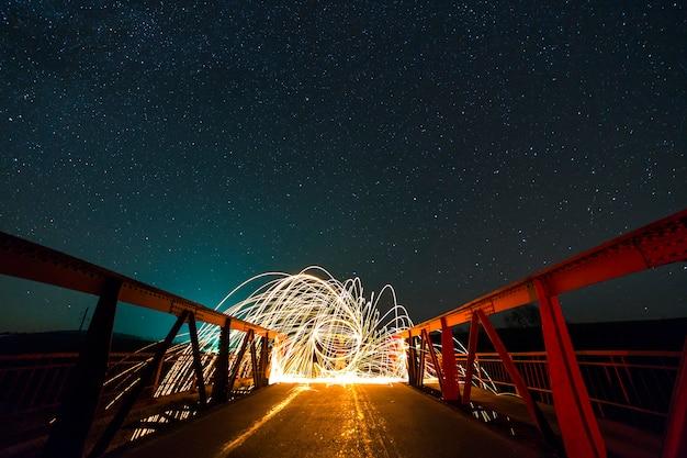 Concept d'art de peinture légère. tir longue exposition de filature de laine d'acier dans un cercle abstrait faisant des feux d'artifice d'étincelles rougeoyantes jaune vif sur un long pont sur le ciel étoilé de la nuit bleue.