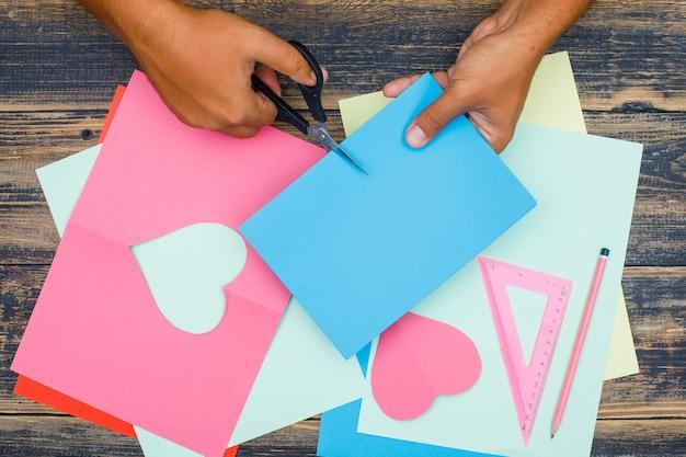 Concept artisanal avec règle, crayon sur fond plat en bois. homme coupe du papier.