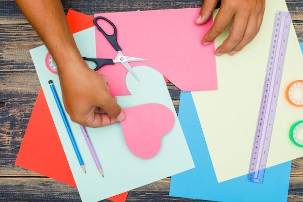 Concept d'artisanat avec des ciseaux, une règle, des bandes, des crayons sur fond plat en bois. homme mettant de côté le papier coupé.