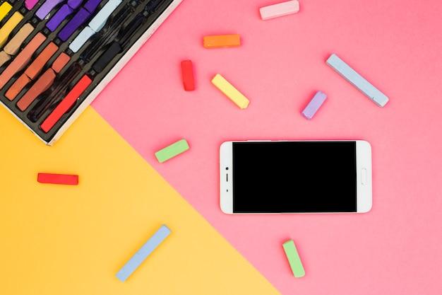 Concept d'artiste charmant avec des craies colorées et smartphone