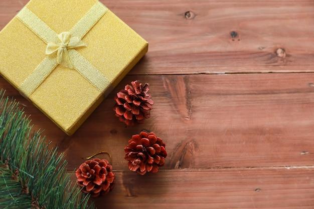 Concept d'assaisonnement de nouvel an, noël et vacances. gros plan d'une boîte cadeau en or avec beau ruban et ornements pommes de pin et arbre de noël sur planche de bois avec espace de copie.