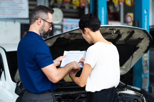 Concept d'assurance automobile. l'agent d'assurance examine la voiture endommagée avec une cliente écrivant des informations sur le formulaire de réclamation.