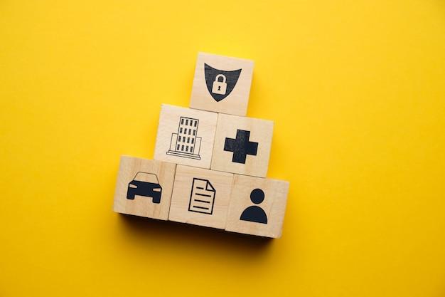 Concept d'assurance automobile, santé, immobilier avec des icônes sur des blocs de bois.