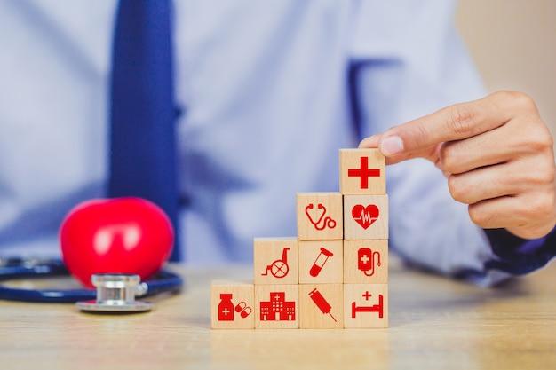 Concept d'assurance maladie, main organisant l'empilement de blocs de bois avec l'icône des soins de santé