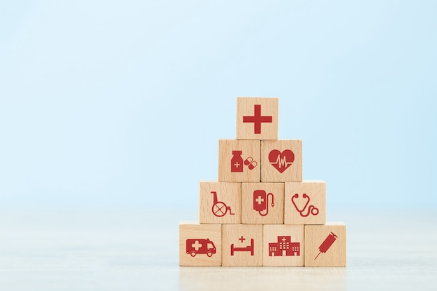 Concept d'assurance maladie, organisant l'empilage des blocs de bois avec l'icône soins médicaux.