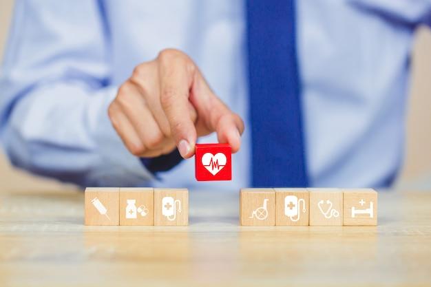 Concept d'assurance maladie, organisant à la main l'empilement de blocs de bois avec l'icône de soins médicaux.