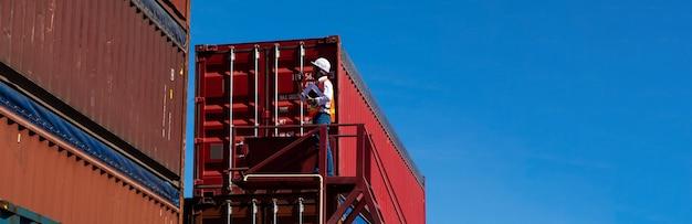 Concept d'assurance maritime et transporteur. le contremaître contrôle le chargement de la boîte de conteneurs au port d'expédition. logistique commerciale concept d'importation et d'exportation.